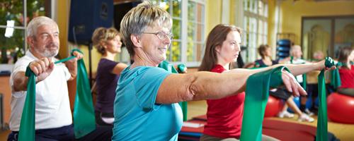 Gruppe im Fitnesscenter trainiert mit Gymnastikband