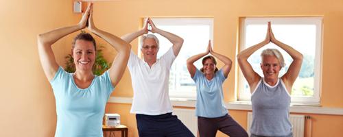 """Yoga-Gruppe im Fitnesscenter macht die Übung """"Vrikshasana"""" (Der Baum)"""