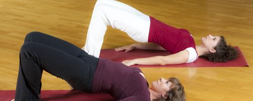 Zwei Frauen machen Gymnastikübungen am Boden
